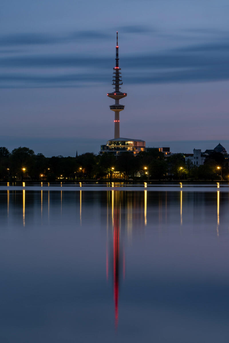 Jan Düerkop: body of water reflecting lights and television tower at dusk.