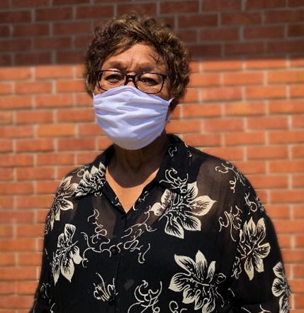 The Potential Within: Jacquelyn Ponder, Black woman with short brown curly hair wearing black glasses, white face mask, and black shirt with white floral patterns