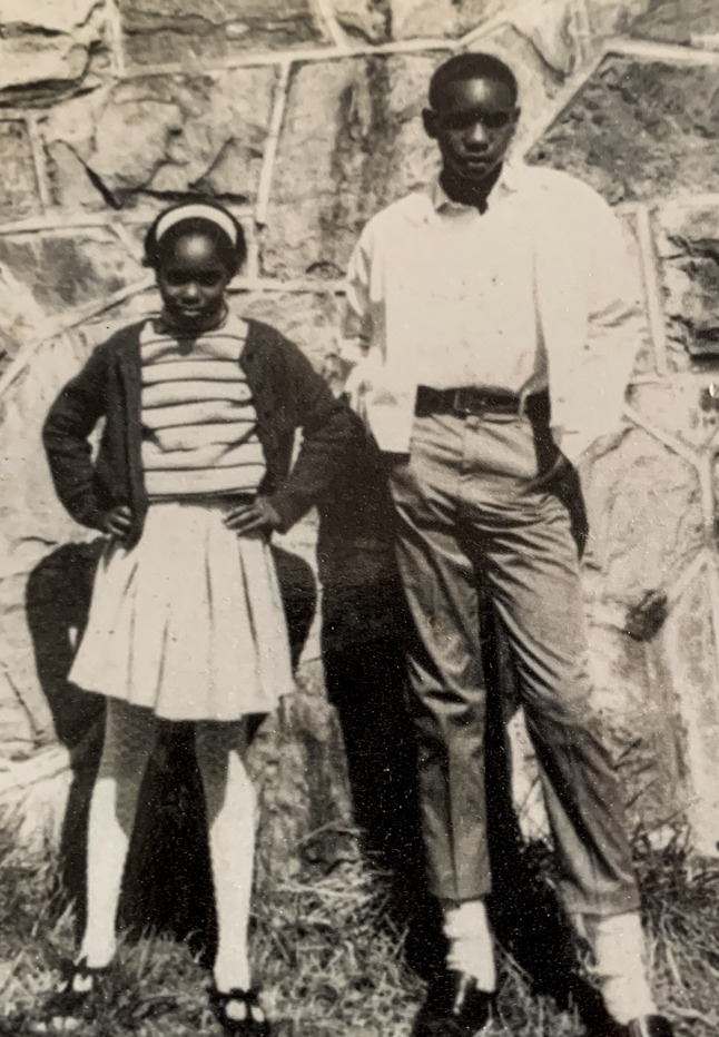 An American Hero: A black teen boy and black pre-teen girl in dressclothes stand in front of a rock wall