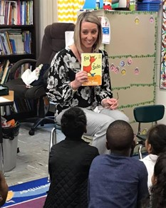 Survivor, Mother, Principal, and Activist: Blonde woman holding a Dr. Sues book sits in chair reading to group of four elementary students sitting on floor of classroom