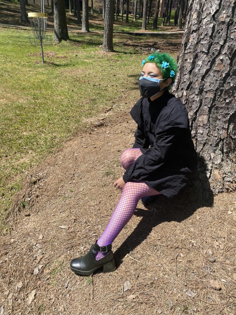 Avery Fields: young woman with with green hair, blue flower hair accessories. Wearing a black dress with purple fishnet leggings and black shoes. Sitting outside beside grass and tree