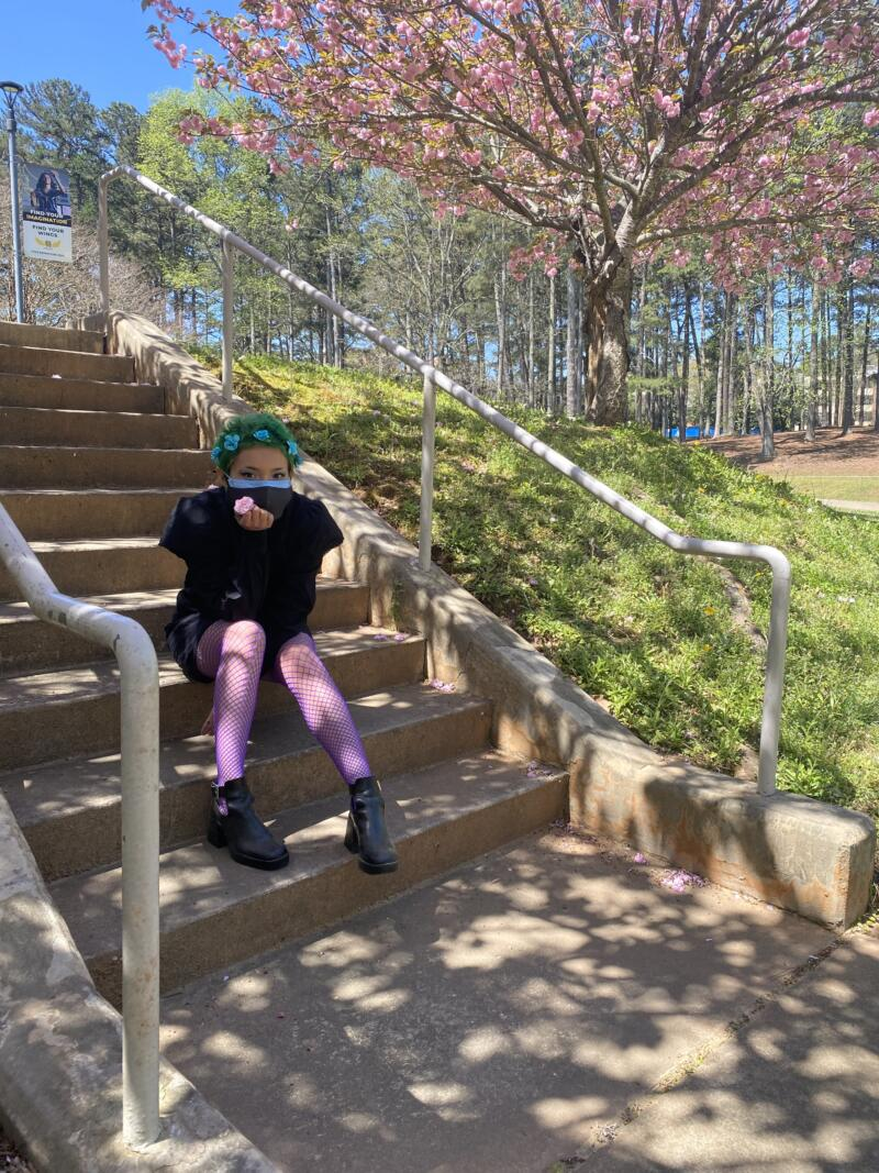 Avery Fields: young woman with with green hair, blue flower hair accessories. Wearing a black dress with purple fishnet leggings and black shoes. Sitting on a staircase outside next to grass, and a tree with pink flowers.