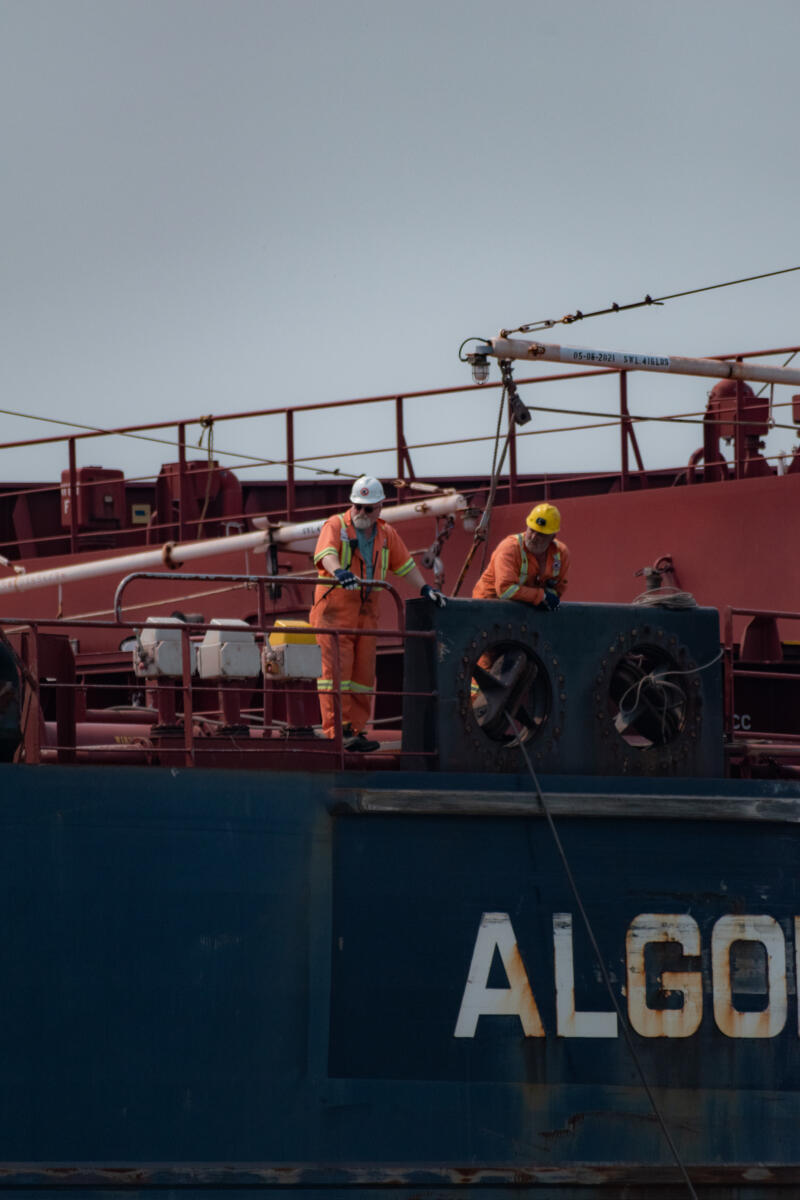Emma Walkington: two men in orange work ship attire looking over the rail of the edge of the ship