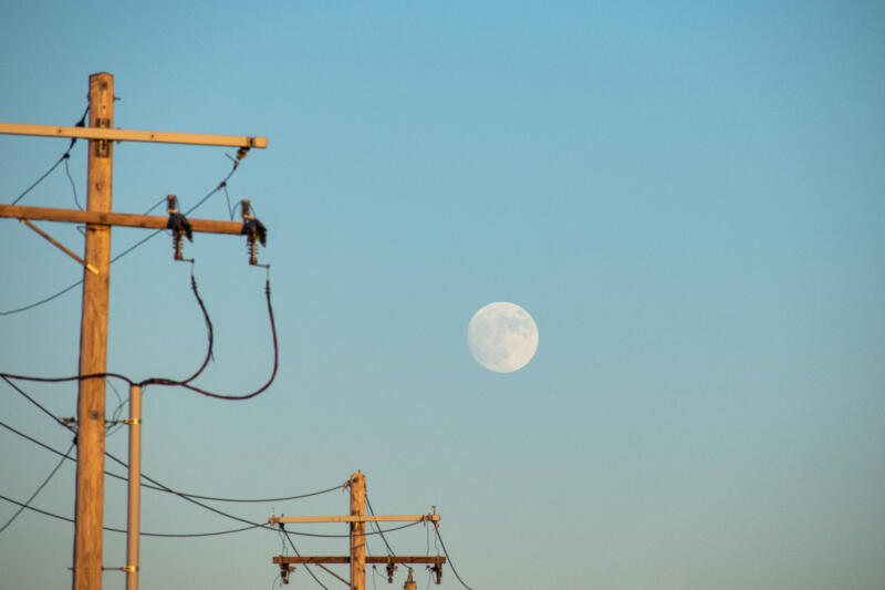 Emma Walkington: Clear gradient blue sky with the moon in the distance. Telephone towers are in the foreground and middle ground.