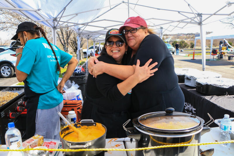 Homeless in Austin, TexasJessica Strickland: Two women, who are Debbie and Laura, are under a large white tarp wearing black clothes and aprons hugging each other behind a table of food in pots .