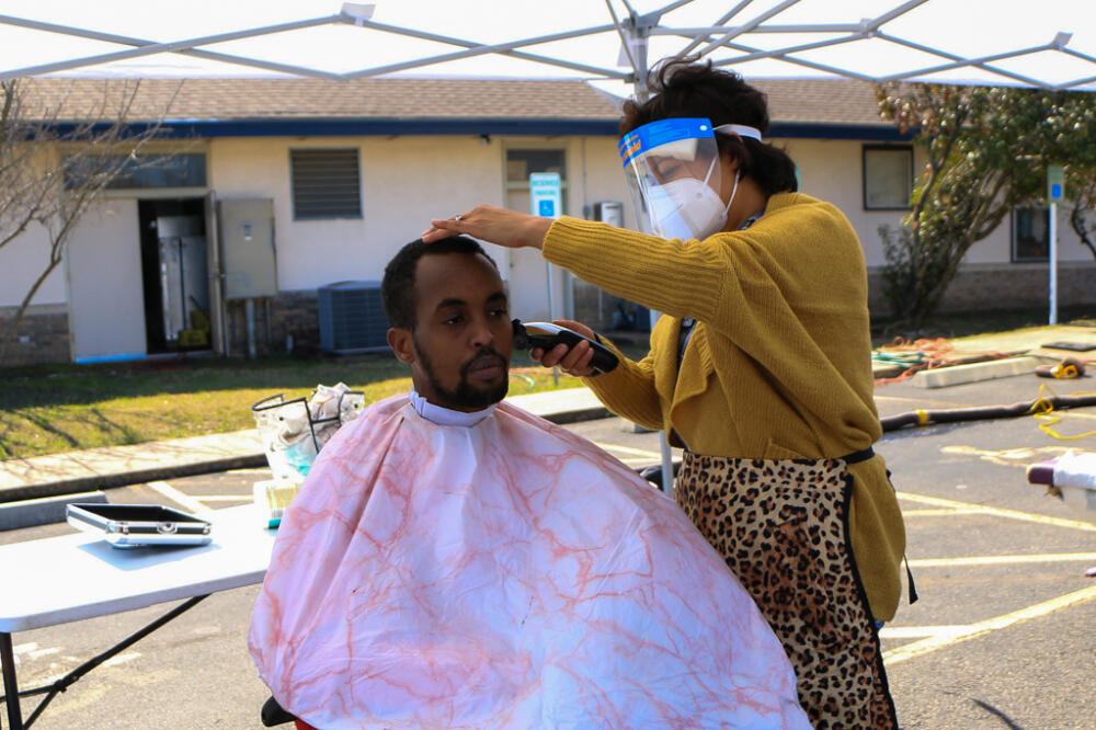 Homeless in Austin, Texas: Black wWoman in yellow coat and face mask giving a haircut to a Black man with pink barber chair cloth on