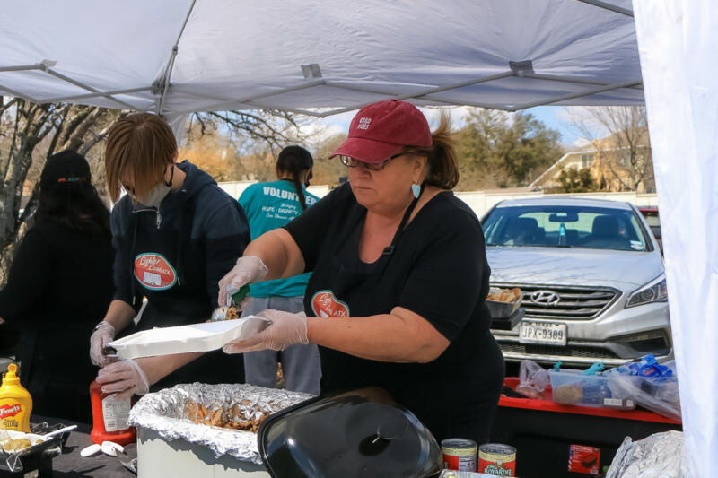 Jessica Strickland: Woman, who is Debbie, wearing a black shirt, red cap and blue earring. She is placing food from a larger container into plate