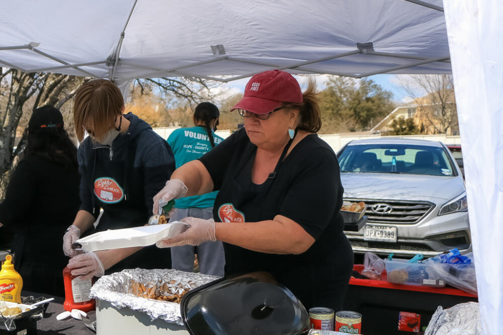 Homeless in Austin, Texas: Woman wearing a black shirt, red baseball cap and blue earring placing food from a larger container into a plastic plate